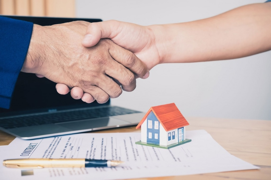 real estate agent shaking hands to his client after signing contract agreement in office,concept for real estate, moving home or renting property